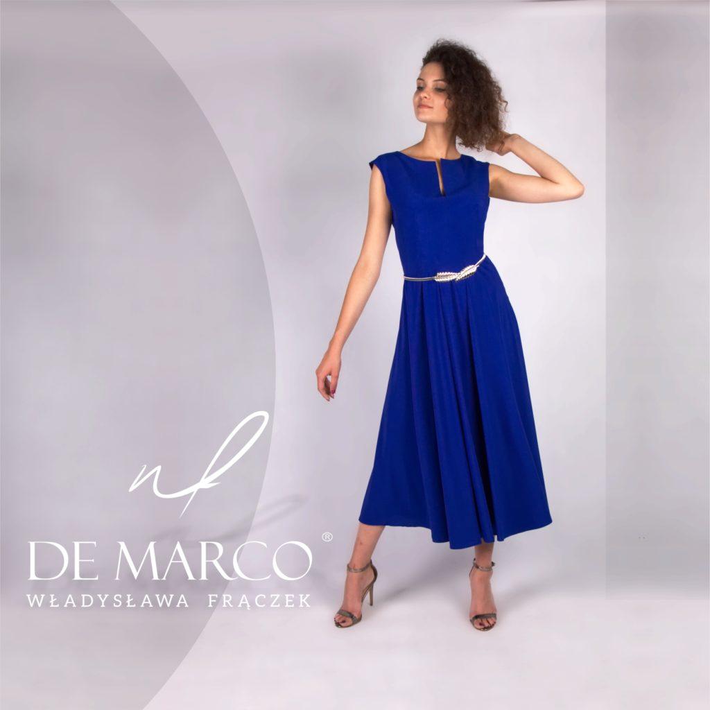 Granatowa nieprzesadzona sukienka dla matki wesela od projektantki mody z De Marco. Stylizacja do połowy łydki z błyszczącym srebrnym paskiem.