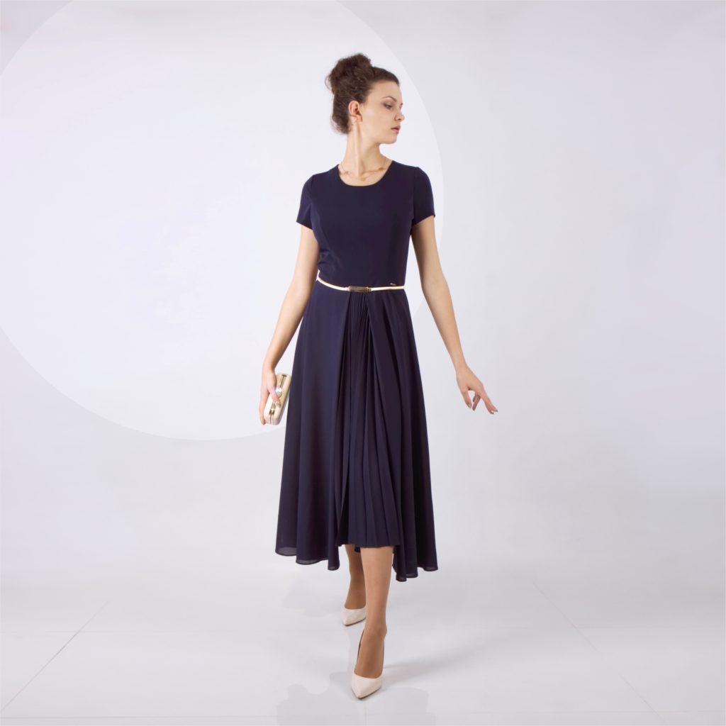 Elegancka granatowa sukienka idealną dla kobiet o figurze gruszą. Klasyczna powściągliwa z ozdobną plisą w pęknięciu poszerzanej kreacji. Pięknie podkreśla talię. W sprzedaży na sklepie internetowym De Marco.